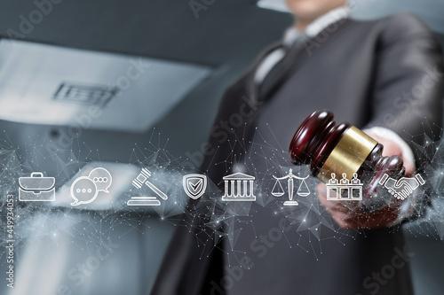 Fototapeta Lawyer holding judge gavel on legal icons background.