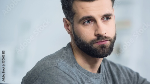 Foto sad and bearded man thinking while looking away at home