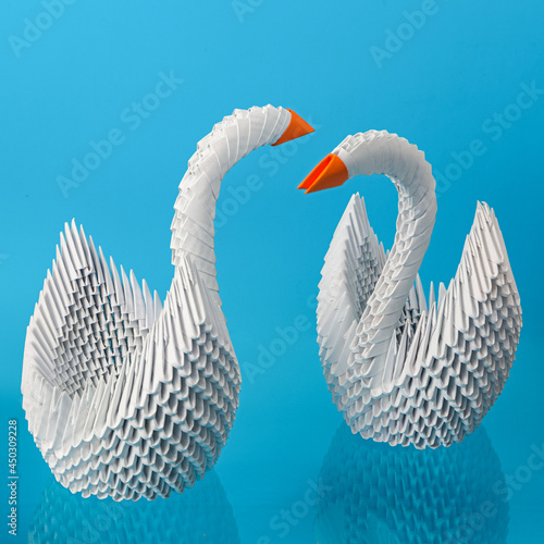 Fototapeta Two white origami swans made of paper with a red beak on a blue background