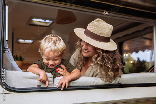 Murais de parede Parent and child in camper van spend time together playing and laughing