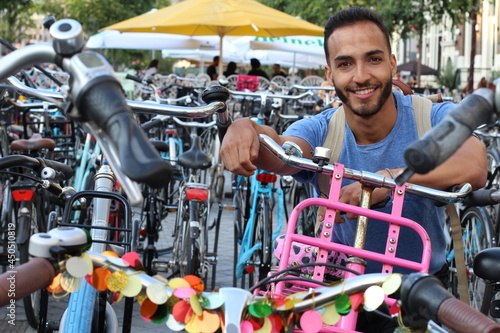 Fototapeta Young ethnic adult in modern bicycle parking lot