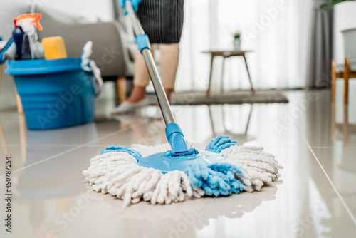 Obraz na płótnie Close up, Housekeeper wearing protective gloves using mop cleaning floor in living room at home, Disinfection and Hygiene Concept