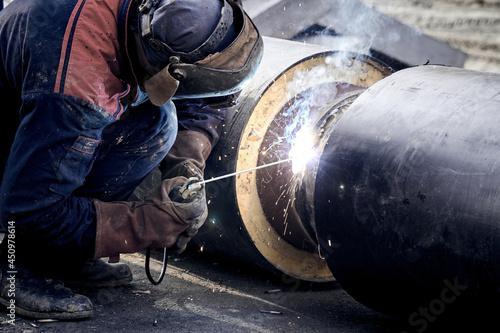 Fotografiet Construction worker arc welding the metal pipe.