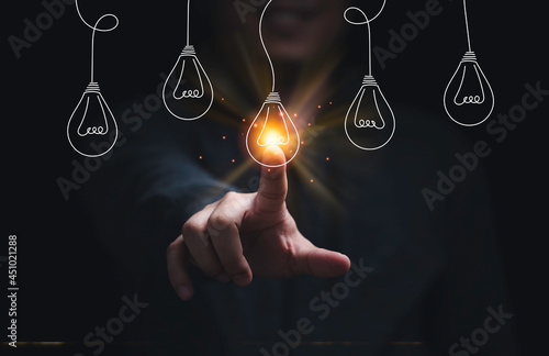 Tela Businessman hand touching glowing lightbulb among lamp does not light for selective creative smart thinking ideas and innovation concept