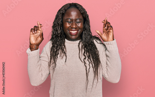 Tablou Canvas Young african woman wearing wool winter sweater gesturing finger crossed smiling with hope and eyes closed