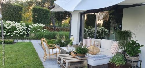 Fotografia Meble ogrodowe na tarasie nowoczesnego domu w pieknym ogrodzie