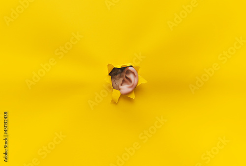 Fotografiet Close-up of a woman's ear through a torn hole in yellow paper