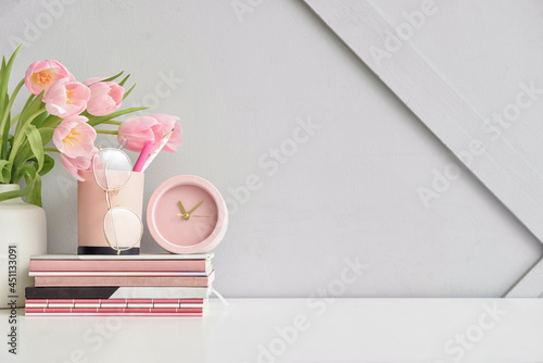 Stylish workplace with notebooks and tulip flowers near light wall