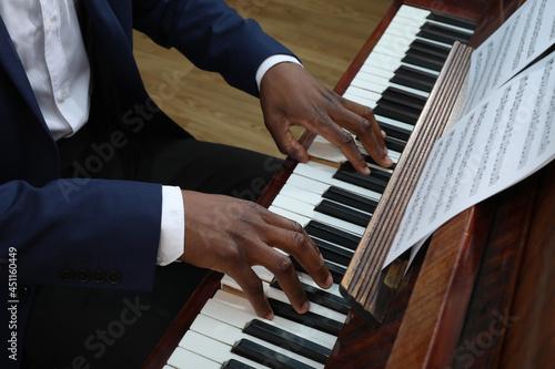 Fotografie, Obraz African-American man playing piano indoors, closeup