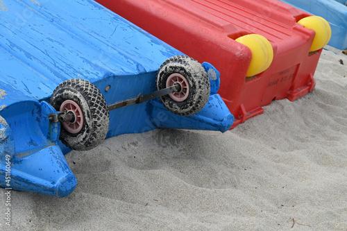 Obraz na plátně Gros plan sur des barques retournées sur le sable avec des roues