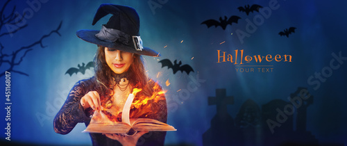 Photo Halloween Witch girl with magic Book of spells portrait