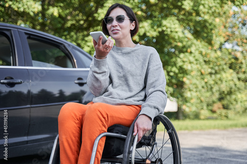Disabled woman sitting at the wheelchair and recording voice message at her mobi Fotobehang