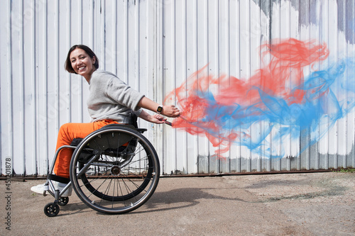 Canvas Girl with loss of leg function moving herself at the wheelchair and smiling