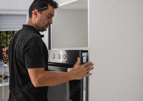 Fotografija Man placing an oven inside the hole of a new kitchen cabinet