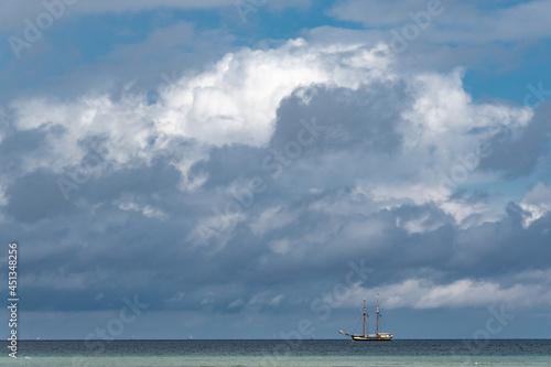 Tela A vintage sailing ship on the horizon under a violent summer sky