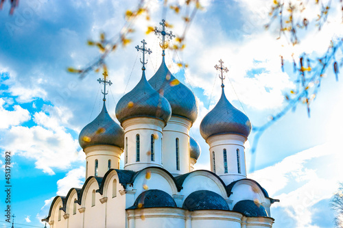 Carta da parati Domes with Eastern Orthodox crosses on a white church against a blue sky with clouds Orthodox Faith