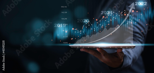 Businessman or trader showing glowing virtual technical investment graph chart for analysis stock market , Banking financial and planing concept Fototapet