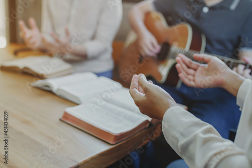 Fototapeta Christian young man group are playing guitar and sings a song from a Christian h