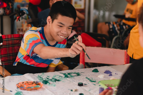 Handicapped teenager boy on wheelchair with happy face doing art work with friends, Lifestyle of smart disabled kid learning activity in special children school, Mental health classroom concept Fototapete