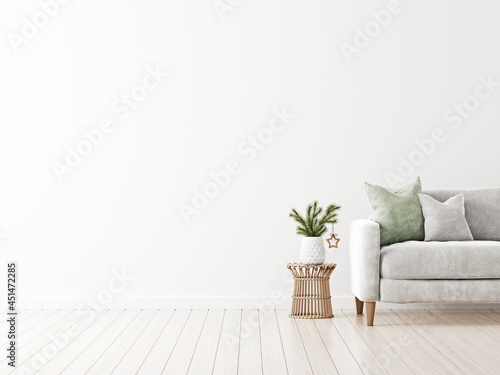 Fototapeta Simple minimalist Christmas interior mockup with grey sofa and fir tree branch in vase with decoration on wicker rattan table on empty white wall background