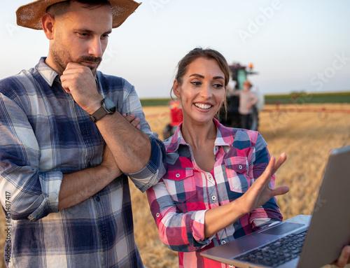 Farmers looking at laptop in field Fototapeta