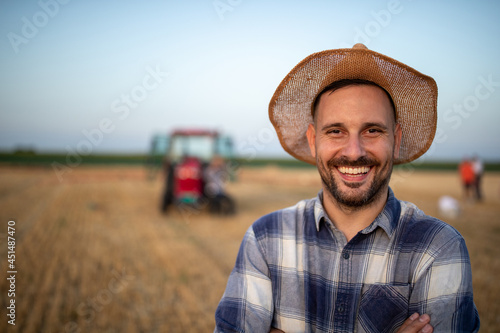Portrait of farmer with straw hat in front of tractor Fotobehang