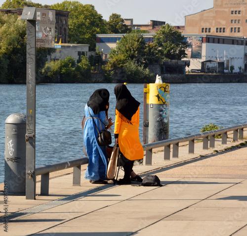 Obraz na płótnie Women in hijab walking in the riverside