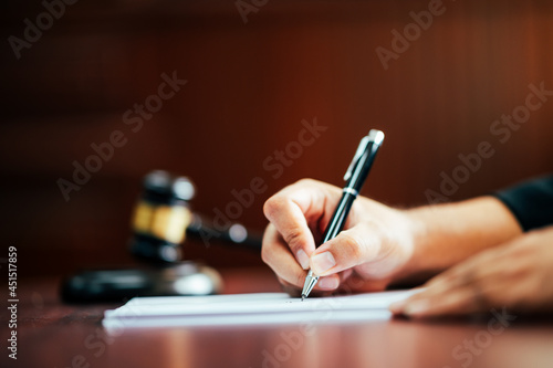 Fototapeta Lawyer holding a pen to write cases in the courtroom