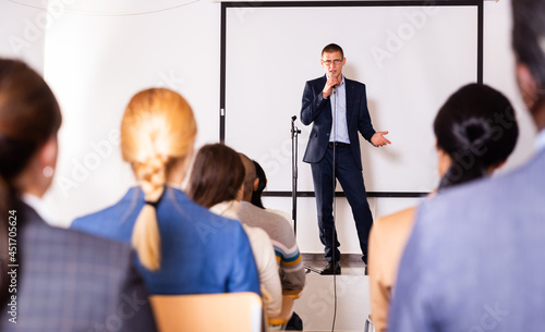 Billede på lærred Confident man with microphone speaking at corporate business event in conference