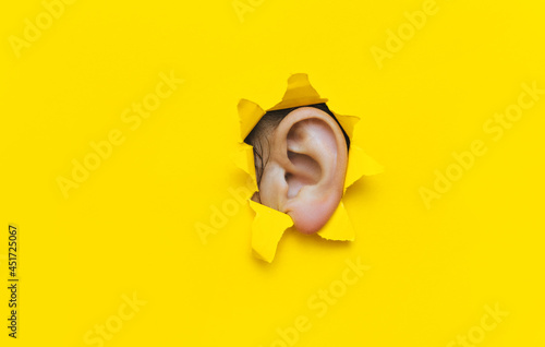 Canvas Close-up of a left woman's ear through a torn hole in yellow paper