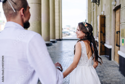 the young bride holds the groom's hand and smiles Fotobehang
