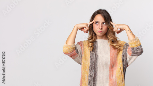Photographie pretty thin woman looking concentrated and thinking hard on an idea, imagining a