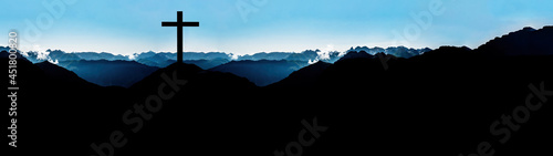 Foto Religious grief landscape background banner panorama - View with black silhouette of mountains, hills, forest and cross / summit cross, in the evening during the sunset, with blue colored sky