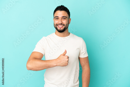 Photographie Young arab man isolated on blue background giving a thumbs up gesture
