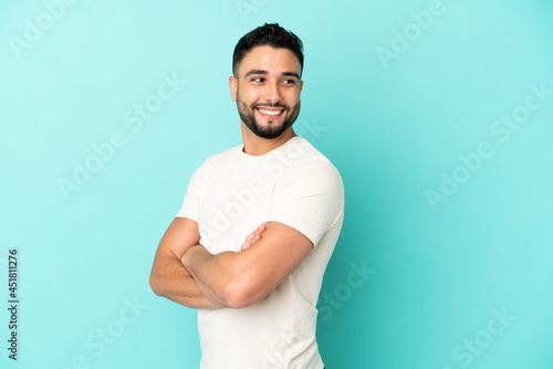 Canvas Print Young arab man isolated on blue background with arms crossed and happy