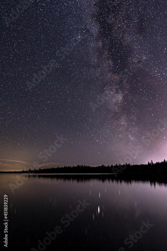 Slika na platnu The Milky Way galaxy appears in the night sky over a calm lake.