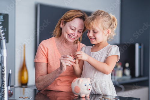 Fényképezés Close up happy older mother and adorable little daughter holding touching pink piggy bank, caring mum and adorable girl child saving money for future, family insurance and investment concept