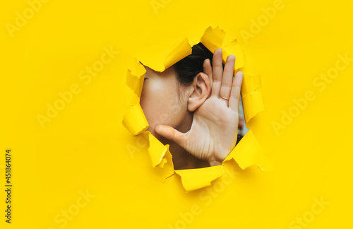 Fotografia, Obraz Close-up of a woman's ear and hand through a torn hole in the paper