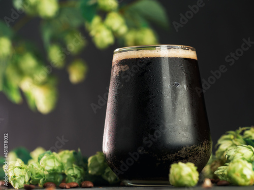 Photo glass of dark beer, craft stout or porter with green hop cones