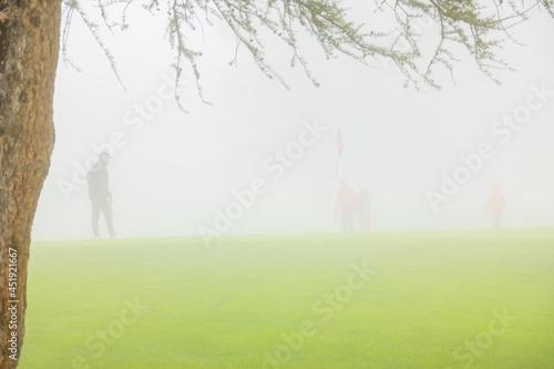 Obraz na płótnie Golfer on Putting Green in Crans Sur Sierre Golf Course with Fog in Crans Montan