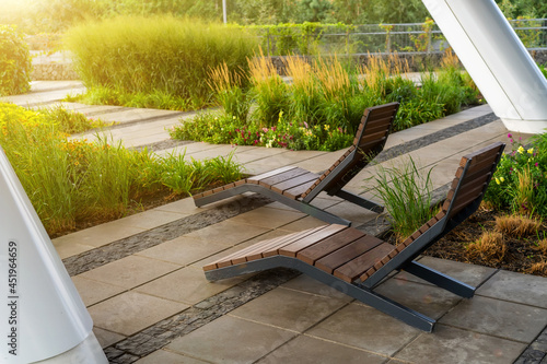 Foto Two empty brown wooden deck chairs or chaise longues on tile among decorative grass and flowers in recreation area