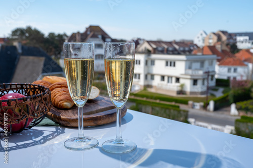 Murais de parede Drinking of brut champagne sparkling wine in flute glasses on outdoor bistro ter