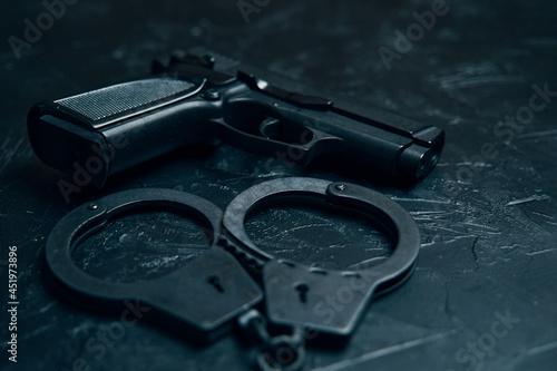 Obraz na plátne Pistol and handcuffs close up on black table