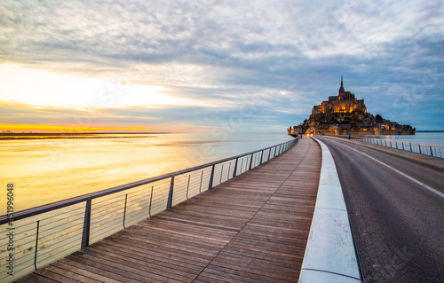 Fototapeta Le Mont Saint-Michel and the bridge over water in Normandy