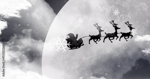 Image of black silhouette on santa claus in sleigh being pulled by reindeer with winter scenery