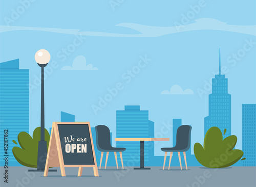 Summer outdoor cafe with table and seats on modern city background Fototapet