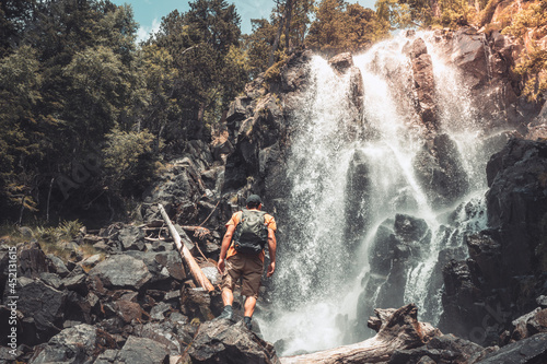 Attractive man standing in front of a big waterfall enjoying the amazing landscape views Fototapeta