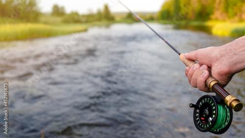 Fotografiet Fly fishing rod in fisherman hand