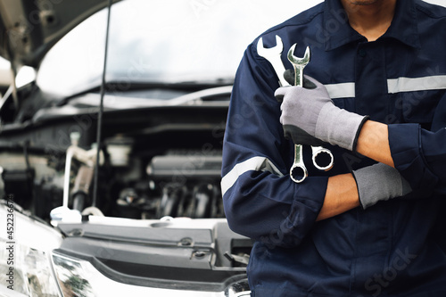 Hand of car mechanic with wrench. Auto repair garage. mechanic works on the engine of the car in the garage. Repair service. Concept of car inspection service and car repair service.