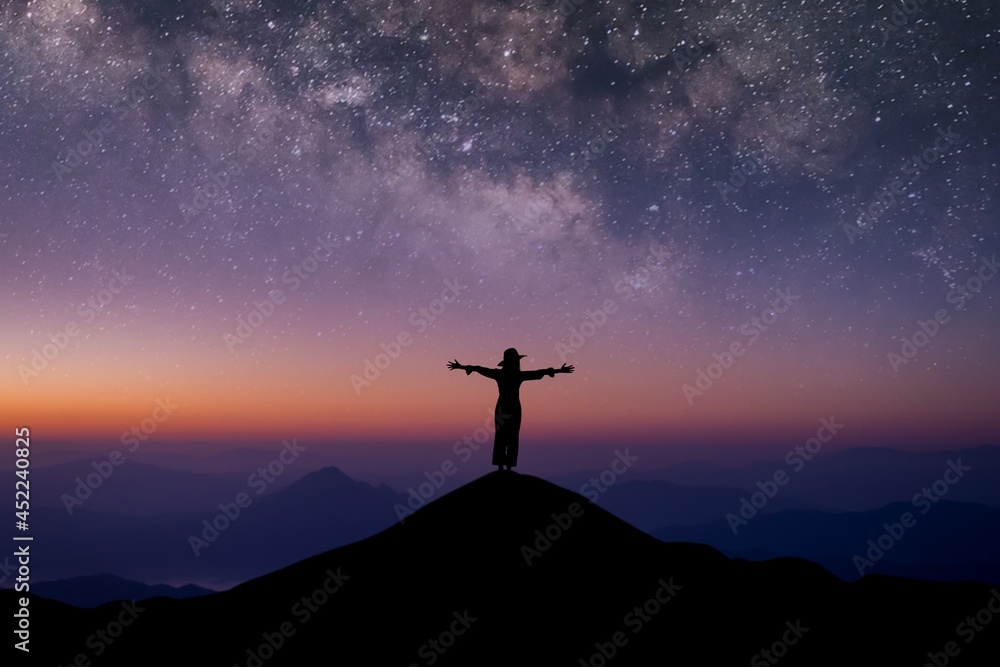Silhouette of young female traveler wearing hat standing and open arms watched the beautiful night sky, star and milky way alone on top of the mountain.